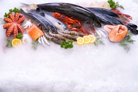 Top view of variety of fresh luxury seafood, Lobster salmon mackerel crayfish prawn octopus mussel and scallop, on ice background with icy smoke in seafood market. Photo With Copy space. Reklamní fotografie - 158638060