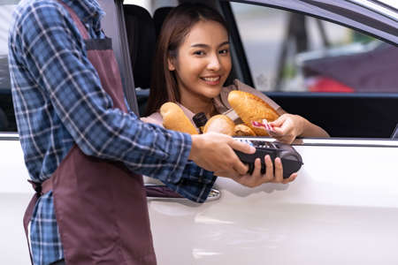 Portrait of asian woman make mobile payment contactless technology for online grocery ordering and drive thru service. Drive through and food online is new normal popular after covid-19 pandemic.