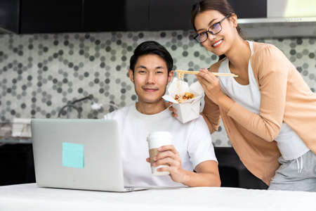 Asian couple work from home in the kitchen with delivery take away food while city lockdown from coronavirus covid-19 pandemic. New Normal lifestyle working from home.