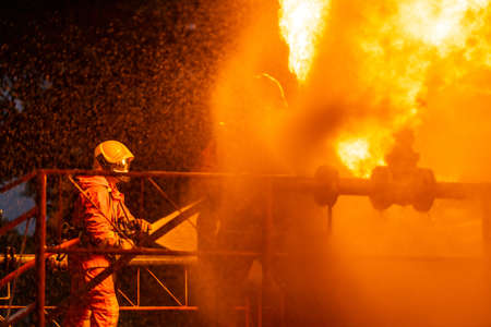 Firefighter using water fog type fire extinguisher to fighting with the fire flame from oil pipeline leak and explosion on oil rig and natural gas station. Firefighter and industrial safety concept. Reklamní fotografie - 158638077