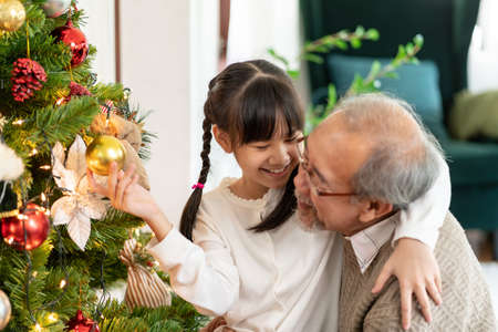Little girl decorating a Christmas tree with her grandfather. They decorating the Christmas tree prepare for season greeting of Merry Christmas. Multigenerational asian Family concept.