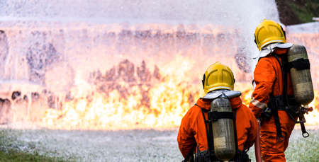 Panoramic Firefighter using Chemical foam fire extinguisher to fighting with the fire flame from oil tanker truck accident. Firefighter safety disaster accident and public service concept. Reklamní fotografie - 158638079