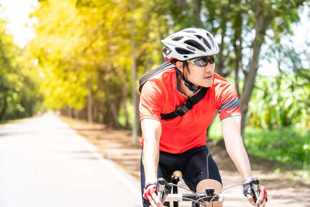 Portrait of asian male cyclist in sportsware shirt cycling along countryside road with green tree in background. Weekend outdoor sport athlete and fitness concept.