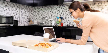 Panoramic Asian woman work from home in the kitchen and eating delivery pizza take away food and take out coffee while city lockdown from coronavirus covid-19 pandemic. New Normal lifestyle. Reklamní fotografie - 158638083