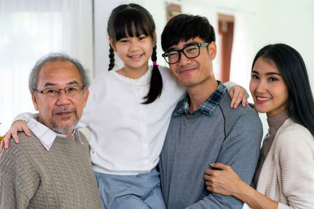 Group Portrait of Happy multigenerational asian family standing in living room with smile in new apartment. Muti genration family happiness concept. Reklamní fotografie