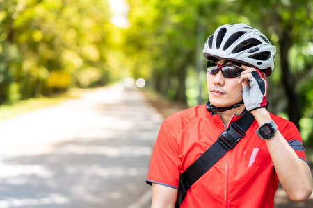 Portrait of asian male cyclist in sportsware shirt with his bicycle in countryside road with green tree in background. Weekend outdoor sport athlete and fitness concept. Reklamní fotografie
