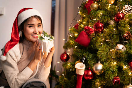 Beautiful asian woman holding Christmas ornament for decorate on christmas tree preparing for season greeting of merry christmas and happy holiday. Reklamní fotografie