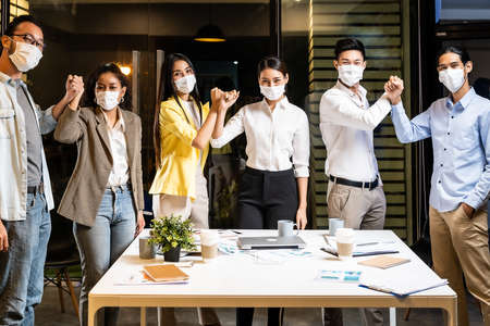 Businessperson do alternative greeting instead of hand shake to reduce infection of coronavirus COVID-19 in new normal office lifestyle in meeting room at night. They wear protective face mask.