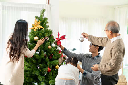 Multigenerational asian Family decorating a Christmas tree. Mom Dad daughter girl and grandfather decorate the Christmas tree prepare for season greeting of Merry Christmas and Happy Holidays. 版權商用圖片