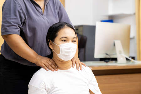Quarantine asian woman do massage at home with face mask while city lockdown for social distance due to coronavirus pandemic. Massage is one of service business that shutdown while city lockdown. 版權商用圖片