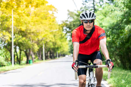 Portrait of asian male cyclist in sportware shirt cycling along countryside road with green tree in background. Weekend outdoor sport athlete and fitness concept.