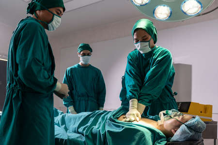 Surgeon doctor and nurse do CPR to patient while patient have problem with Sudden Cardiac Arrest while surgery in Operating Room OR. Medical health care Surgery concept.