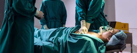 Panorama Surgeon doctor and nurse do CPR to patient while patient have problem with Sudden Cardiac Arrest while surgery in Operating Room OR. Medical health care Surgery concept.