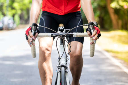 Close up of asian male cyclist in sportware shirt cycling along countryside road with green tree in background. Weekend outdoor sport athlete and fitness concept. Reklamní fotografie