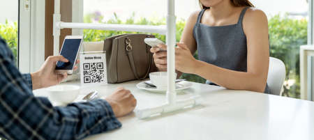 Panoramic Asian customers scan QR code online menu. Customers sat on social distancing table for new normal lifestyle in restaurant after COVID-19 pandemic.
