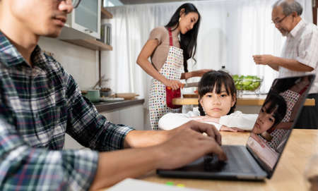 Portrait Asian upset girl waiting her father working from home while city lockdown in dining room while mom and grandfather cooking in kitchen. Domestic life multigenerational family concept.