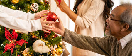 Panoramic Close up hand little asian girl decorate Christmas tree with grandfather prepare for season greeting of Merry Christmas and Happy Holidays. Multigenerational Family engage happiness concept.