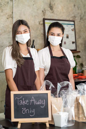Portrait of waitress wear protective face mask smiling with take away or takeout food sign. This essential service is very popular while city lockdown from coronavirus COVID-19 Pandemic 版權商用圖片