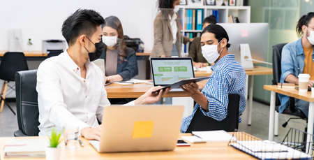 Panoramic Group of interracial business worker team wear face mask in new normal office with social distance practice with hand sanitizer alcohol gel on table prevent coronavirus COVID-19 spreading 版權商用圖片