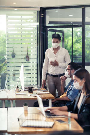 Group of interracial business worker team wear protective face mask in new normal office with social distance practice with hand sanitizer alcohol gel on table prevent coronavirus COVID-19 spreading