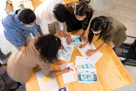 Top View Interracial asian business team brainstorming idea at office meeting room after reopen due to coronavirus COVID-19 city lockdown. They wear face mask as new normal lifestyle.