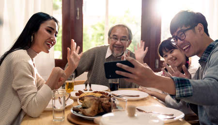 Happy asian multigenerational family of dad mom daughter girl and grandfather taking selfie together before eating lunch together at home.  Happy family engagement togetherness concept. 版權商用圖片