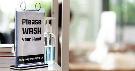 Panoramic Signage of Hand Sanitizer around office for hygiene practice after reopen with blurred background of business people working and wear face mask in new normal office life prevent covid-19.