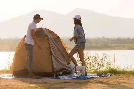 Young adult Asian couple pitch and set up tent for camping around the lake. Camping trip with dog outdoor activity campsite concept. 版權商用圖片