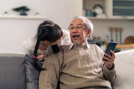 Happy retirement elderly man sitting on sofa at living room with granddaughter using digital tablet together. Multigenerational family with technology concept. 版權商用圖片