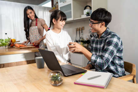 Asian little girl serving water to her dad while working with computer laptop and mom cooking in kitchen. Family Work at home while quarantine from COVID-19. Happy family togetherness concept.