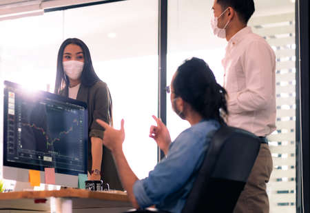 Three asian business person discuss their work in morning after office reopen due to coronavirus COVID-19 pandemic. They wear protective face mask to prevent infection. New normal office life concept. Reklamní fotografie