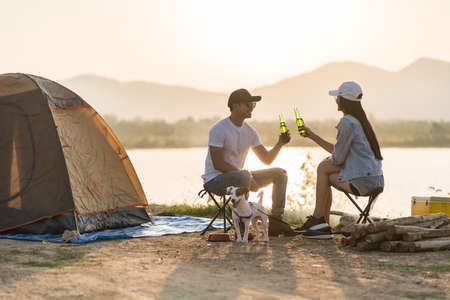 Young adult Asian couple drinking beer beside their tent campsite while sunset. Camping trip with dog outdoor activity campsite concept. 版權商用圖片