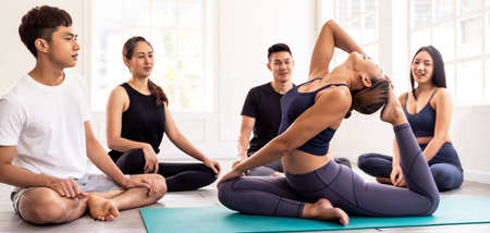 Panoramic asian yoga instructor coach wearing sportswear bra pants do king pigeon pose in yoga studio with her students in background. Work out fitness healthy lifestyle concept.