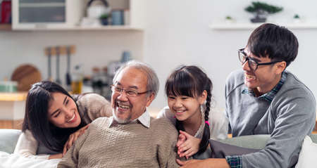 Panorama Group Portrait of Happy multigenerational asian family sit on sofa couch in living room with smile. Muti genration family happiness concept. 版權商用圖片
