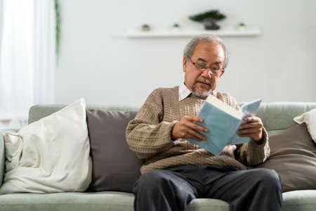 Happy asian retirement elderly man sitting on sofa at living room reading fiction book. Domestic senior life at home. 版權商用圖片