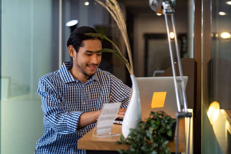 Young adult Asian businessman sitting at coffee bar in office with laptop. Smart office work everywhere concept.