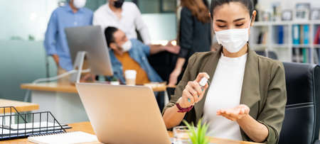 Panoramic Asian office employee businesswoman wear face mask use alcohol spray hand sanitizer for hygiene in new normal office with social distance practice prevent coronavirus COVID-19 spreading. 版權商用圖片
