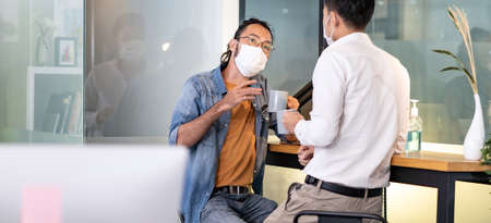 Panoramic Two office workers talking while coffee break in new normal with social distance practice office.  They wear face mask reduce risk to infection of COVID-19 coronavirus as new normal life.