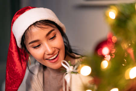 Beautiful asian woman holding Christmas ornament for decorate on christmas tree preparing for season greeting of merry christmas and happy holiday. 版權商用圖片