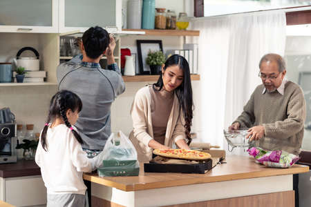 Happy asian multigenerational family of dad mom daughter girl and grandfather setting up dining table before meal. Asian happy family doing domestic life together.
