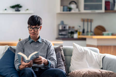 Happy asian young adult man sitting on sofa at living room reading fiction book. Domestic life relax at home.