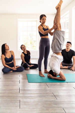Asian people learning Yoga class in fitness club. Instructor coaching and adjust correct head stand pose to student at front while others looking. Yoga Practice Work out lifestyle concept. 版權商用圖片