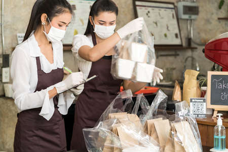 Asian waitress wear protective face mask prepare food for takeout and curbside pickup orders while city lockdown from coronavirus COVID-19 pandemic. This is essential service while lockdown.