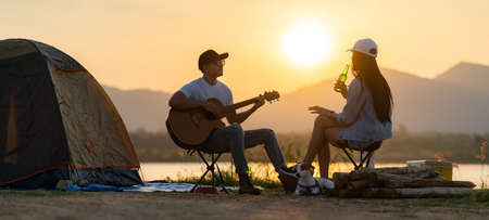 Panoramic Young adult Asian couple playing guitar and drinking beer beside their tent campsite while sunset. Camping trip with dog outdoor activity campsite concept.