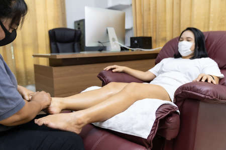 Quarantine asian woman do foot massage at home with face mask while city lockdown for social distance due to coronavirus pandemic. Massage is one of service business that shutdown while city lockdown.