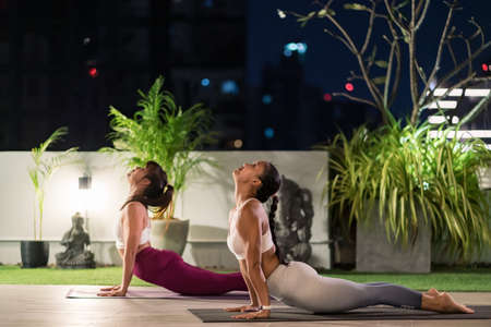 Two asian women in sportswear pants practicing yoga during city lockdown in their apratment with distance in background of cityscape illumination at night. Work out fitness healthy lifestyle concept.