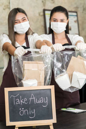 Close up waitress wear protective face mask smile and hold shopping bag for take away or takeout food. This essential service is very popular while city lockdown from coronavirus COVID-19 Pandemic 版權商用圖片