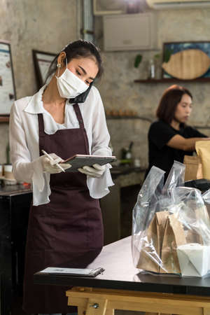 Asian waitress take order from mobile phone for takeout and curbside pickup orders while city lockdown. They wear protective face mask to prevent from infection of coronavirus COVID-19 pandemic. 版權商用圖片