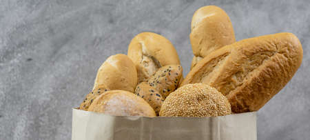 Variety bread in disposable paper bag on grey vintage loft background. Bakery food and drink and grocery concept for delivery. Panoramic web banner crop.