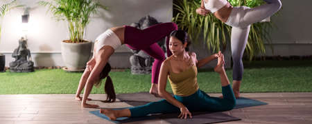 Panoramic Group of asian women in sportswear pants practicing yoga in their apratment with distance in background of cityscape illumination night. Work out fitness healthy lifestyle concept